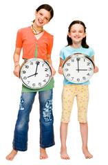 Smiling girls holding clocks