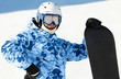 Snowboarder in ski suit and helmet with snowboard
