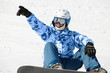 Snowboarder in ski suit and helmet sits on snowy hillside