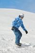 Snowboarder slides down snowy ski slope on snowboard.