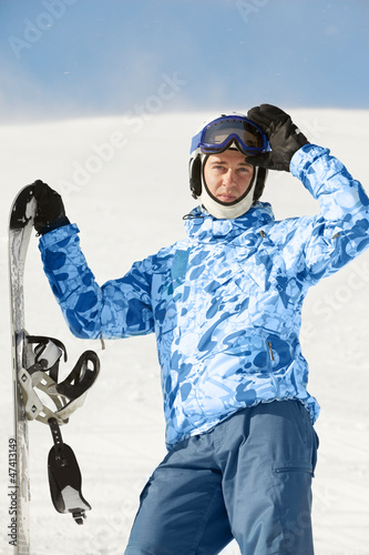 Snowboarder in ski suit and helmet stands with snowboard