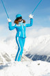 Young woman in blue ski suit stands  on top of hill