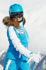 Young smiling woman inski suit poses against snowy mountain