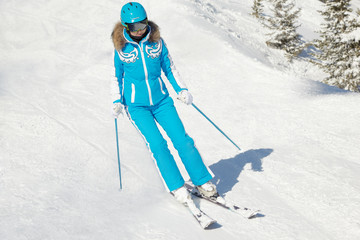 Young woman in blue ski suit and blue helmet skis