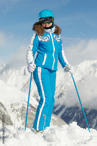 Young smiling woman in blue ski suit poses on top of snowy hill
