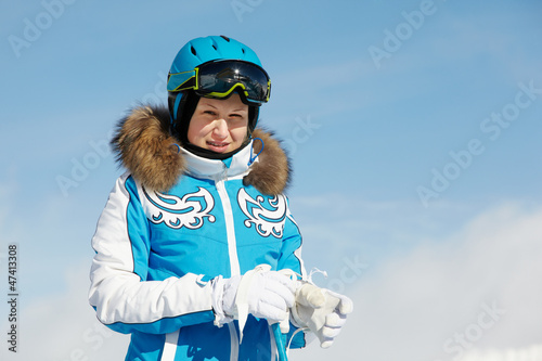 Young woman in blue ski suit stands on background of blue sky