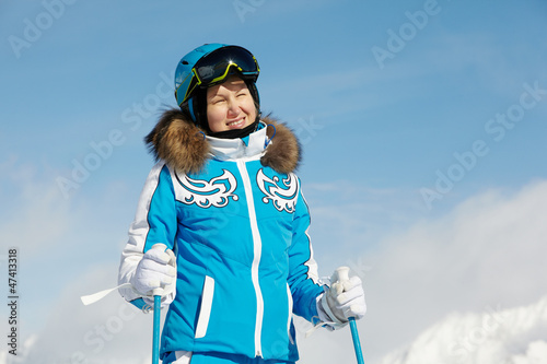 Young smiling woman in blue ski suit stands and looks