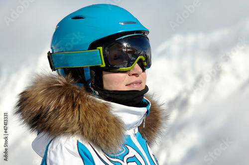 Portrait of young woman in ski suit, helmet and sunglasses
