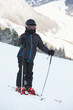 Boy skier in ski suit and helmet stands on snowy slope