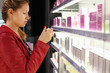 woman with braid chooses perfume in small perfume shop.