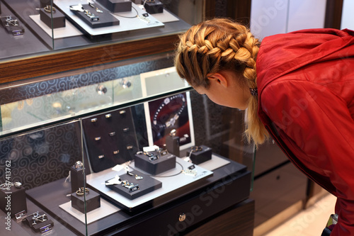 woman with braid considers jewelry in a jewelry store.