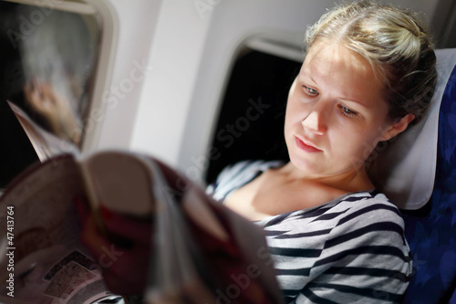 Young beautiful woman reads magazine in airplanee