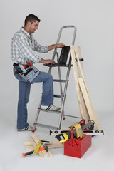 Carpenter using a laptop whilst stood by ladder
