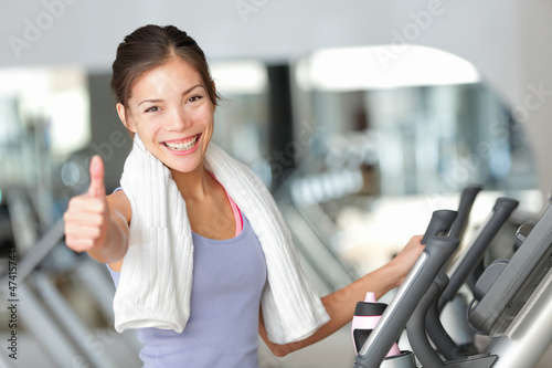 Happy fitness woman thumbs up in gym