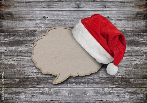 blank recycled paper speech bubble with Santa hat on wood backgr