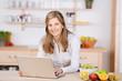 lächelnde frau mit laptop in der küche