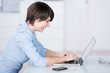 lächelnde frau im büro schaut auf ihren laptop