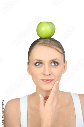 Young woman balancing a green apple on her head