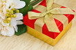 Festive gift box with flowers on wooden  background
