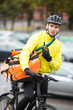 Male Cyclist With Courier Bag Using Walkie-Talkie On Street