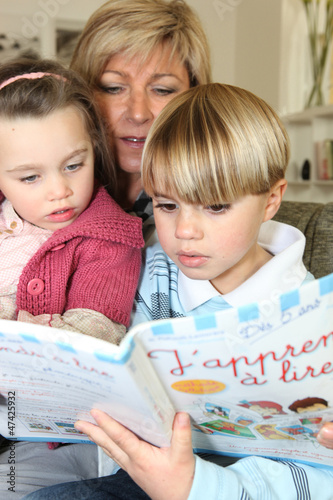 Mother read book with her two children