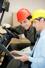 Male Supervisor And Forklift Driver Using Laptop