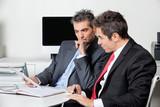 Thoughtful Businessmen Using Digital Tablet At Desk