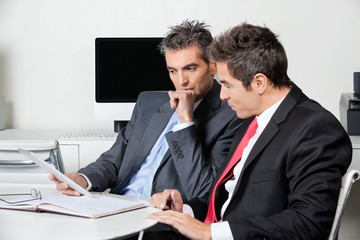 Thoughtful Businessmen Using Digital Tablet At Desk