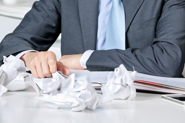 Businessman Sitting At Desk With Crumpled Papers