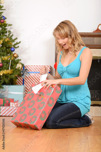 Blonde woman opening christmas present