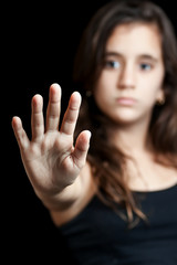Hispanic girl with a hand extended signaling to stop