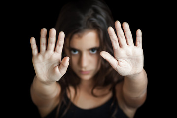 Hispanic girl signaling to stop isolated on black