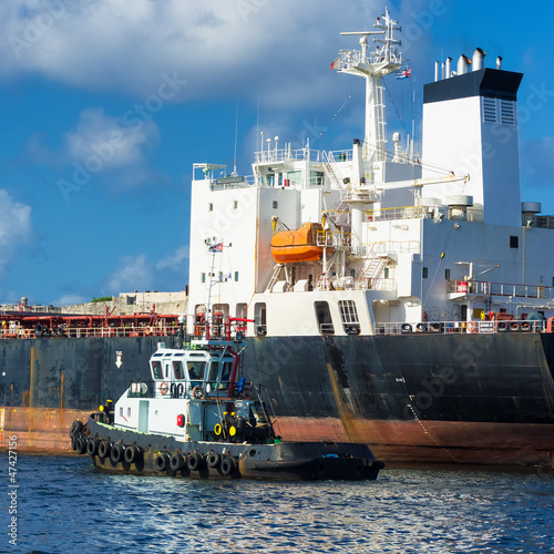 Tugboat guiding a huge cargo ship