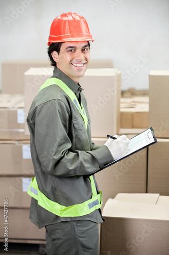 Supervisor Writing Notes At Warehouse