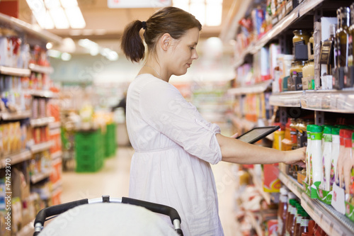 Mid Adult Woman Using Digital Tablet At Supermarket