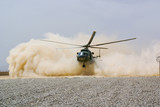 helicopter landing in cloud of dust of desert