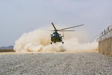 helicopter landing in cloud of dust on desert