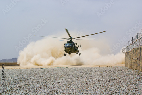 Foto op Canvas Helicopter helicopter landing in cloud of dust on desert