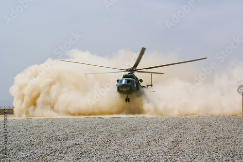Tuinposter Helicopter helicopter landing in cloud of dust of desert