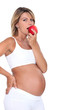 Pregnant woman biting into red apple