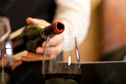 Waiter serving red wine with bottle at the restaurant