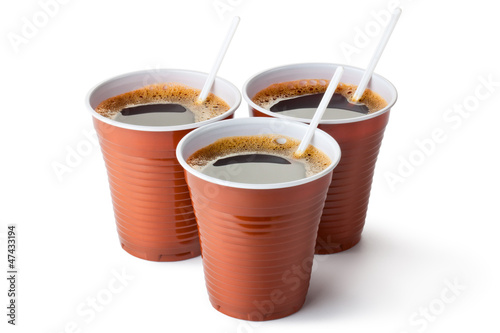 Three plastic vending cups filled with coffee