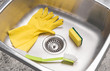 Gloves, sponge and brush in a clean kitchen sink
