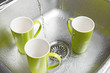 Washing green cups in the kitchen sink
