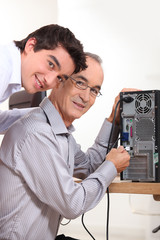 grandson and grandfather connecting a computer
