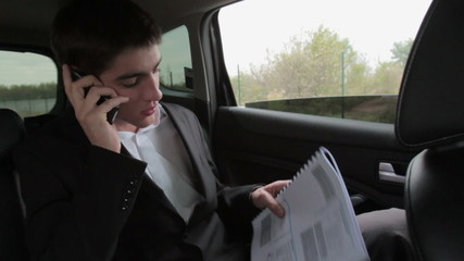 Busy businessman with documents and mobile phone in car