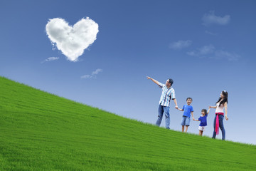 Family stroll in park under heart clouds