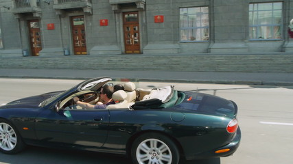 Happy young couple riding in a convertible in the city