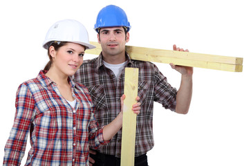 male and female carpenters carrying timber