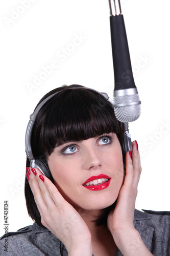 Woman singing into a studio microphone